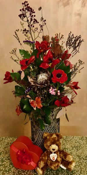 Composizione di fiori con orsetto e vaso in ceramica